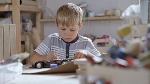Medium shot of boy of primary school age trying to understand how cables work in his toy car in attempt to repair it