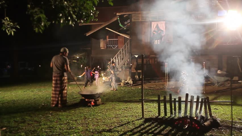 Men making Malaysian traditional food 'lemang' over firewood outdoor kitchen during Eid Mubarak with kids playing firework around vintage village house.Eid ul-Fitr night scene. | Shutterstock HD Video #1009039994