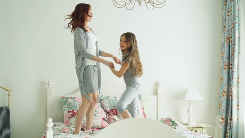 Happy family of cute daughter and young mother jumping and dancing on bed while have fun during holidays at home | Shutterstock HD Video #1009046384