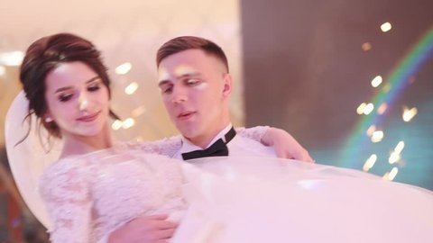 Beautiful Brunette Bride and Handsome Groom Dancing First Dance at the Wedding Party