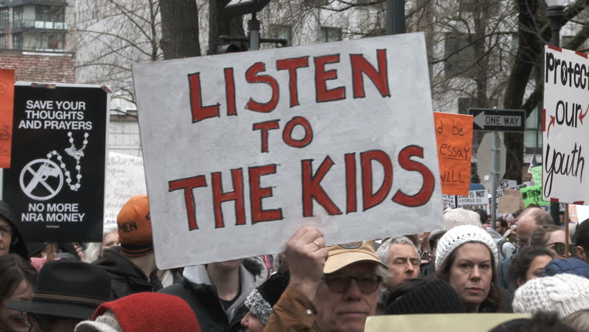 """PORTLAND, OREGON / USA - MARCH 24, 2018: Man holding """"Listen To The Kids"""" sign marching with crowd at March For Our Lives rally."""