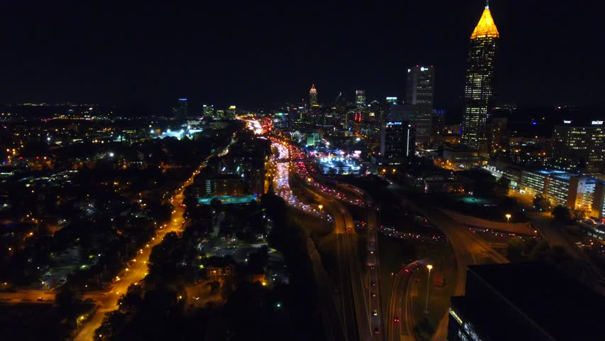 Static shot of the lit up nighttime Atlanta Skyline with traffic below. Freway headlights. Downtown view. Camera hovering in the air.Georgia USA