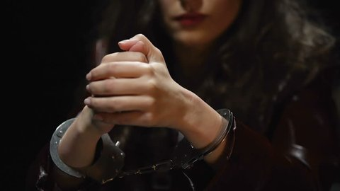 Impudent bored woman sitting in interrogation room, warming up wrists in cuffs
