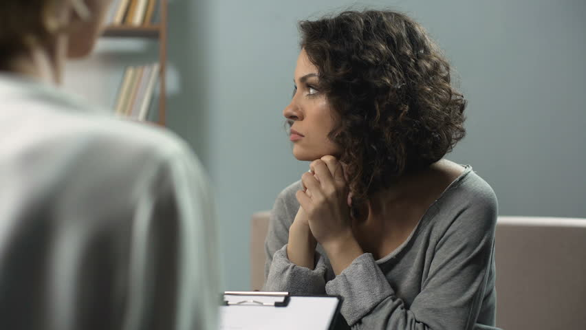 Melancholic woman talking with psychologist at therapy session, depression
