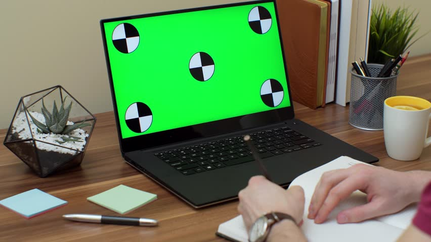 Close up of the shoulder view on man writing in the notebook with a pencil and the laptop computer with a green screen. Office room. Chroma key   Shutterstock HD Video #1009144934