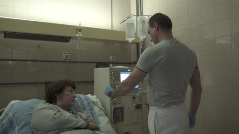 Male medical technician prepares hemodialysis machine for female patient treatment, pan left on the room with nurse and group of mature women that lying in the beds during peritoneal dialysis, indoors