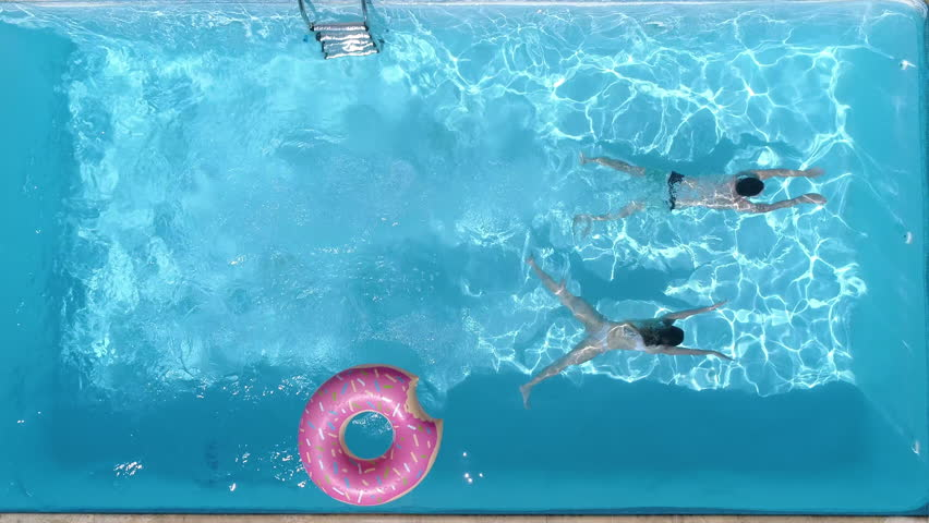 Aerial - Couple diving in the pool at the same time. A fun summer day in the pool at home (slow motion)