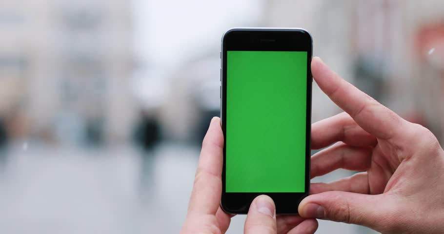 Man holds a smartphone with green screen in his arms standing on the street | Shutterstock HD Video #1009232954