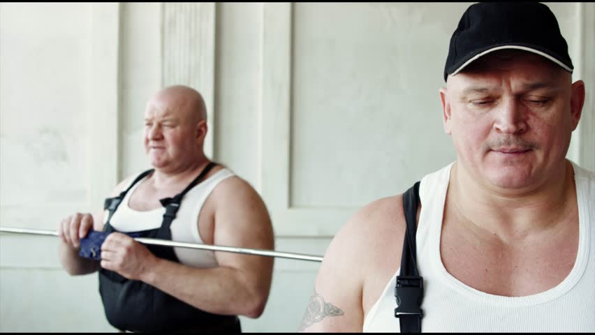 a thick and pumped-up man bends an iron stick with his teeth, next is a builder standing like a bandit or a gangster who holds a toothpick in his hands