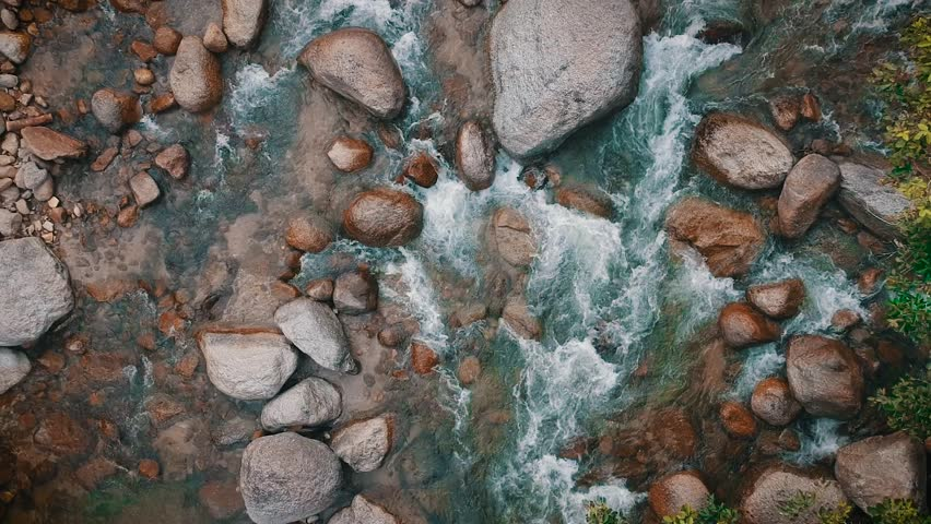 Scenic aerial view of water stream through the stones inside the jungle