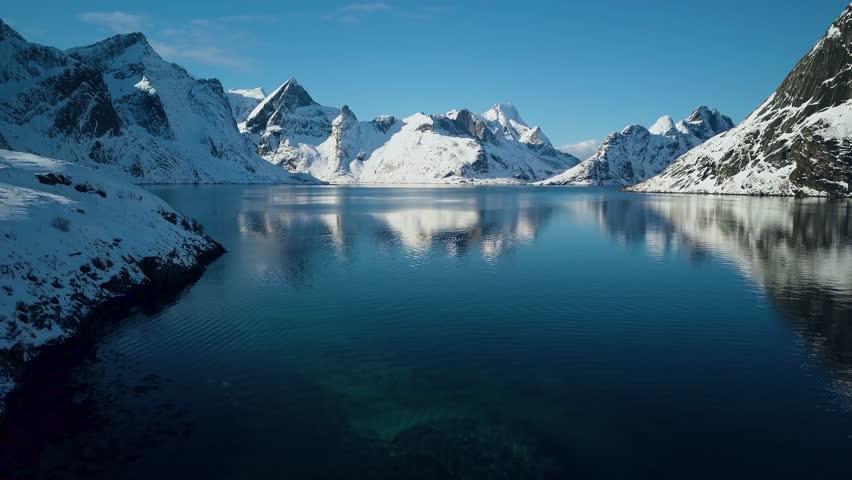 Breathtaking snow covered mountains of Reine, Norway.  Lofoten Islands archipelago in winter.  4k Aerial drone footage | Shutterstock HD Video #1009267604
