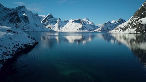 Breathtaking snow covered mountains of Reine, Norway.  Lofoten Islands archipelago in winter.  4k Aerial drone footage