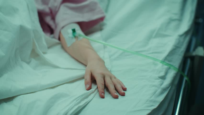 Mother Takes and Holds Hand of Her Sick Little Girl who Is Sleeping in the Hospital Bed. Sad and Hopeful Emotional Moment in Pediatric Ward. Shot on RED EPIC-W 8K Helium Cinema Camera.