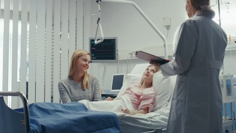 Recovering Little Girl Lies on a Bed In the Hospital, Friendly Doctor With Clipboard Asks Where it Hurts, Mother Sits Beside Bed. Cute Child in the Modern Pediatric/ Children Ward.