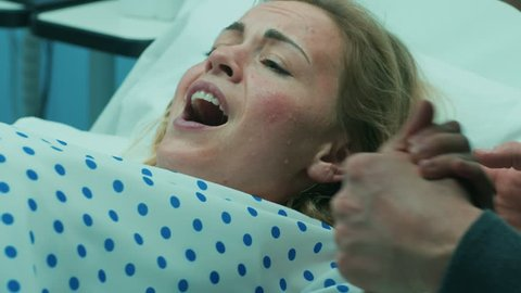 Close-up on a Face of a Woman in Labor Pushing Hard to Give Birth, Husband Holds Her Hand. Woman in Pain, Has Contractions. Shot on RED EPIC-W 8K Helium Cinema Camera.