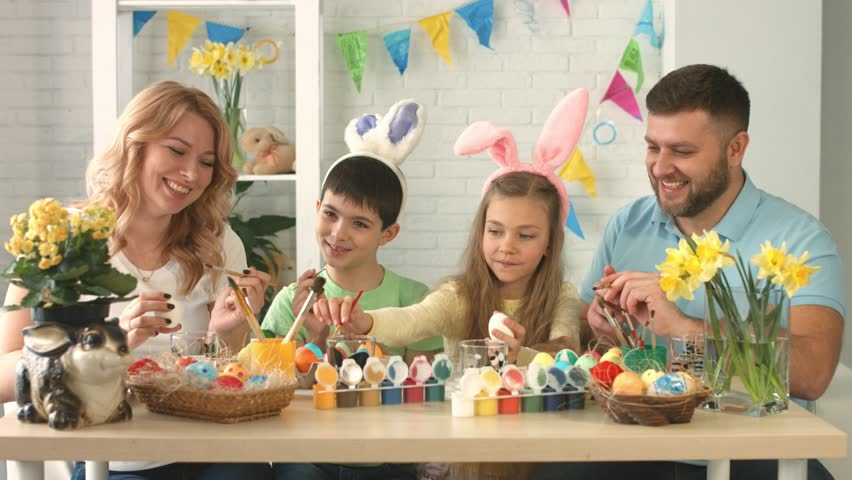 Portrait of a happy family with two children drawing on Easter eggs | Shutterstock HD Video #1009294334