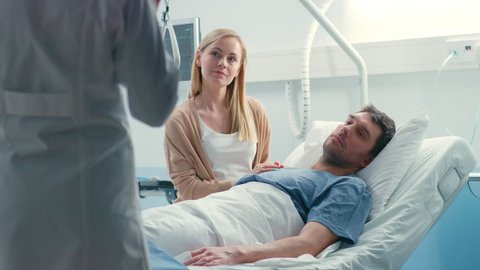 In the Hospital, Patient Lying in Bed, his Wife Sitting Beside, They Listen to Doctor's Explanations. Love and Care Concept. Shot on RED EPIC-W 8K Helium Cinema Camera.
