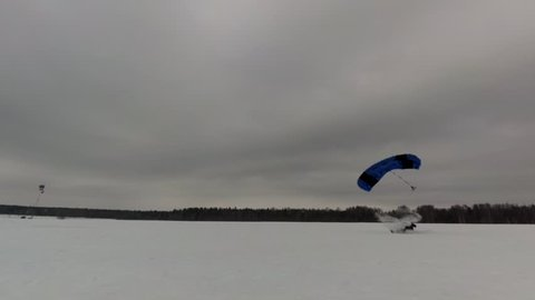Slow motion 0.25x. Skydiver is landing into wet snow.