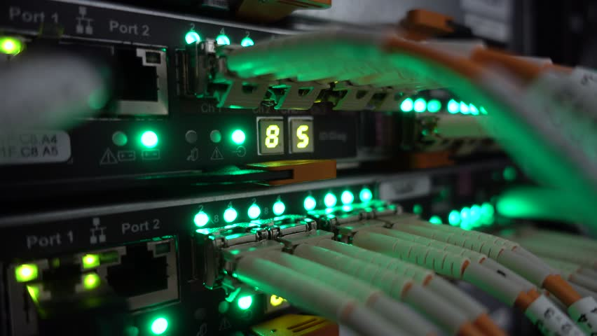 Modern network switch with cables. Flashing server lamp, switch, router. Severs computer in a rack at the large data center. Optical server.