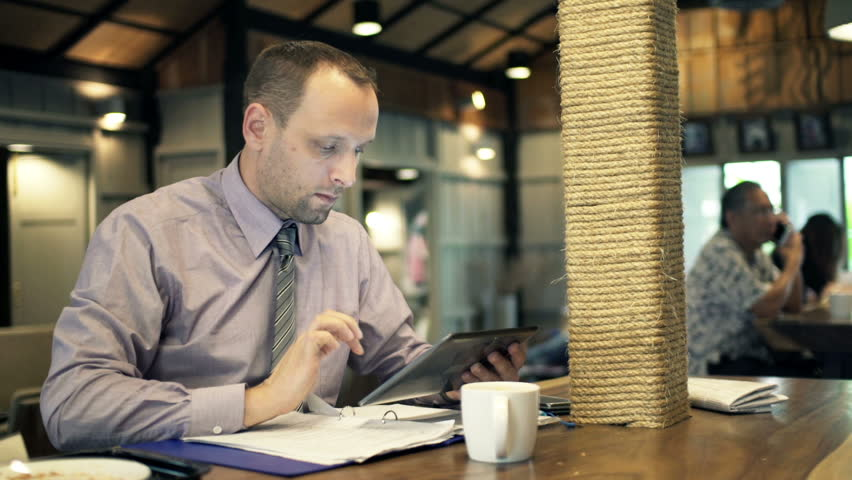 Businessman comparing data on tablet and documents in cafe  | Shutterstock HD Video #10093184