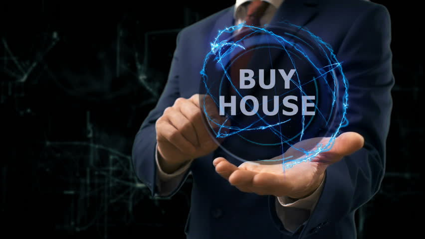 Businessman shows concept hologram Buy house on his hand. Man in business suit with future technology screen and modern cosmic background