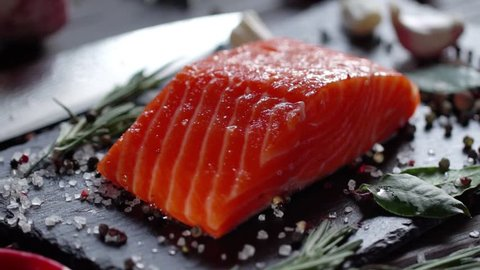 Preparation of salmon steak. Spice and salt sprinkled on a raw piece of salmon. Camera moves around the object. Slow motion 120 fps video.