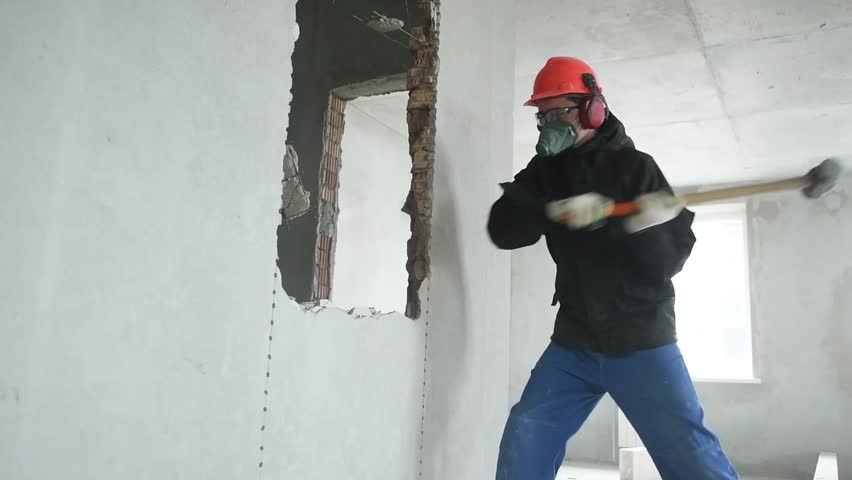 Demolition work and rearrangement. worker with sledgehammer at wall destroying | Shutterstock HD Video #1009348964