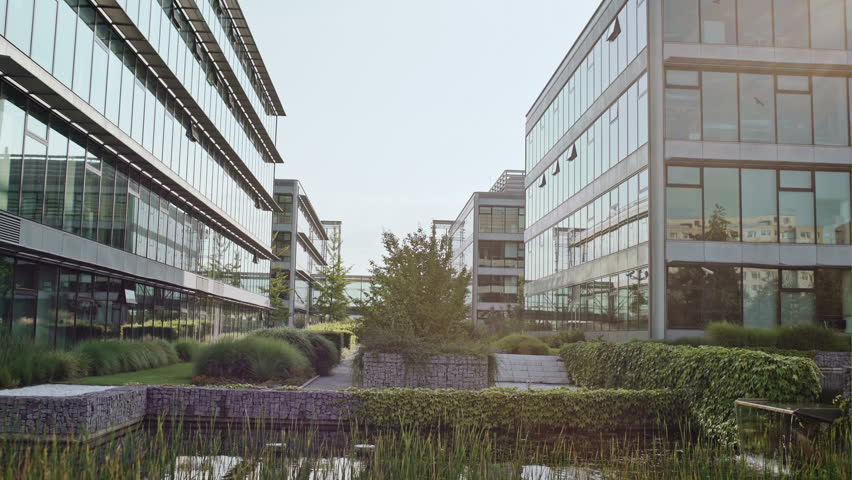 Beautiful artificial pond in office courtyard, with lots of green plants. Camera tilt up to glass office buildings and clear sky