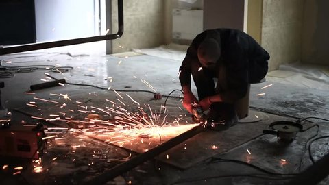 Man works circular saw. Flies of spark from hot metal. The man's hard work. Man Chlef and smooth surface. Man worked over the steel. close-up of hand and electric saws metal. Close-up of hand tool.