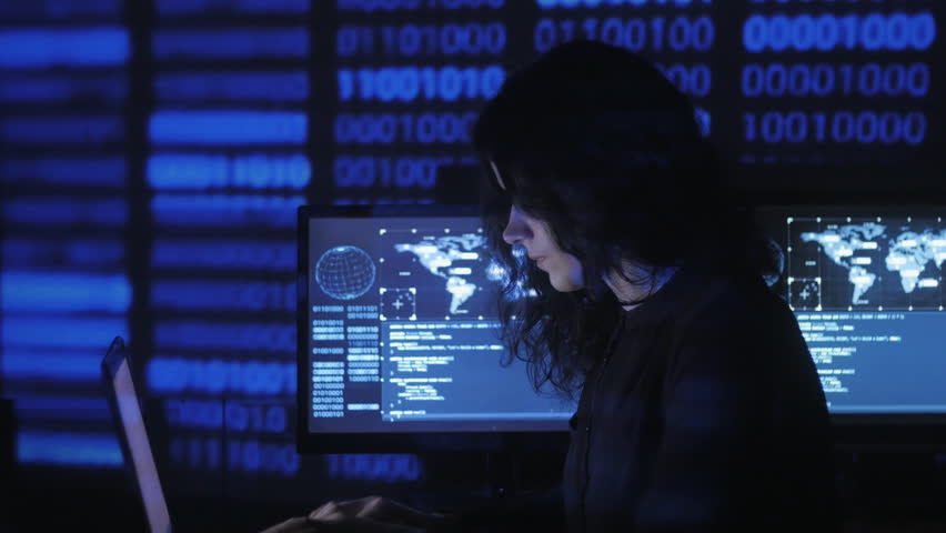 Portrait of young woman programmer working at a computer in the data center filled with display screens | Shutterstock HD Video #1009357994