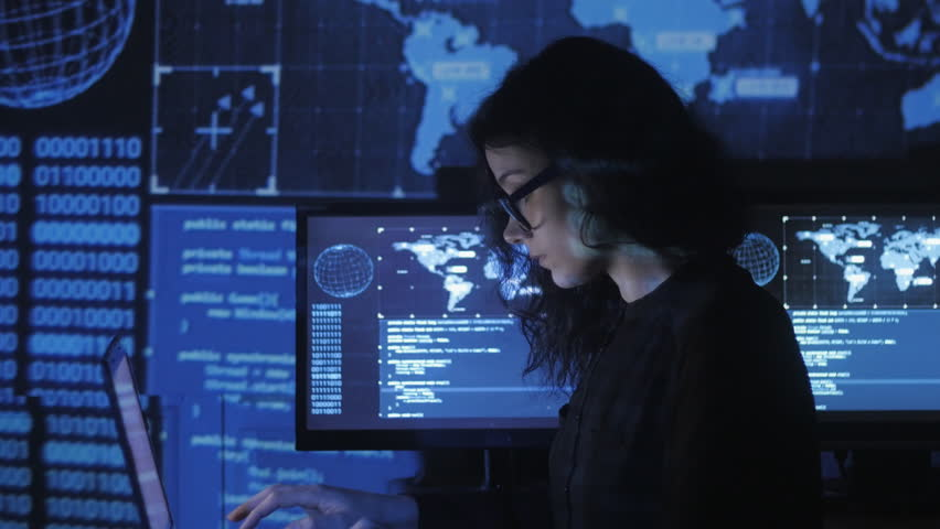 Portrait of young woman programmer in eyeglasses working at a computer in the data center filled with display screens | Shutterstock HD Video #1009358024