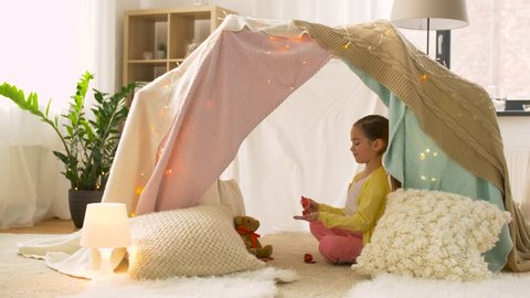 childhood, hygge and friendship concept - happy little girl in kids tent or teepee playing tea party with toy crockery and teddy bear at home