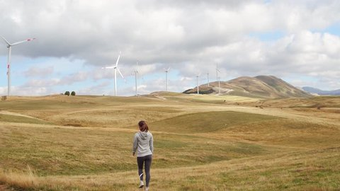 Woman walking on the field with Wind Turbines over a sunset background. Alternative renewable energy production
