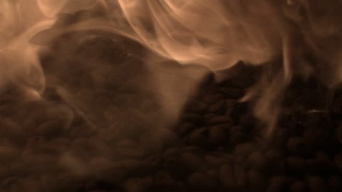 A slow motion shot of flames building up with roasted coffee beans in the background.