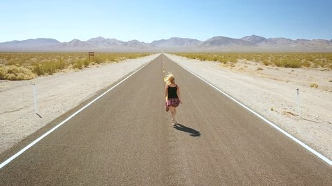 woman dancing alone on street in the middle of nowhere. death valley