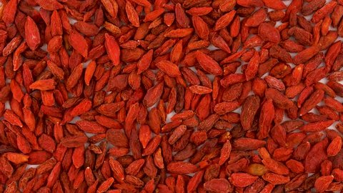 Full frame background of organic dried goji berries rotating on turn table. Loopable. Close up macro. View from above/overhead.