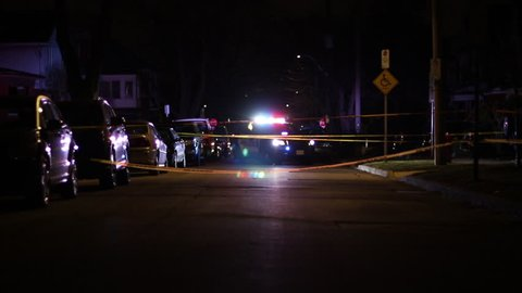 Police car with flashing lights at a taped off crime scene at night on a city street.  Police crime scene investigation.