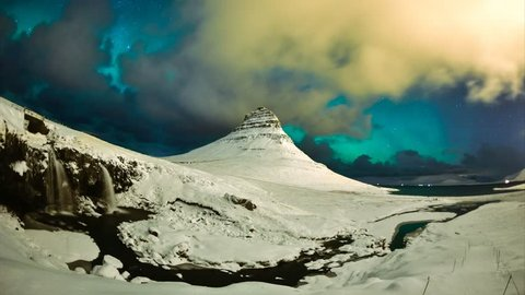 Northerrn lights in Iceland - stormy clouds and aurora borealis above Kirkjufell mountain time lapse 4K