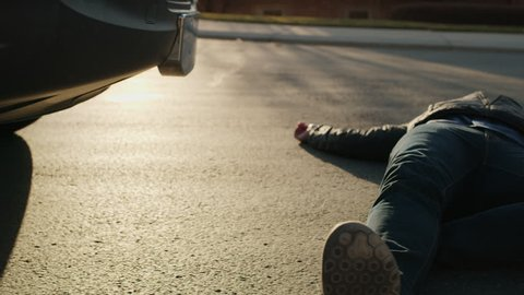 Man laying in street with cell phone near car bumper after accident / Cedar Hills, Utah, United States