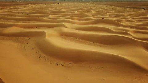 Flying over sand dunes in Sahara desert to the rising sun, Africa