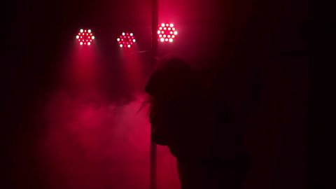 Two sexy girls with long flowing hair dancing around the pole in a night club by the light of red lights. Pole dance.