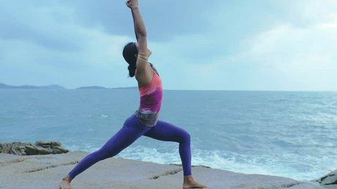 Woman in yoga exercises salutation to sun Surya Namaskar: worship with eight points Ashtanga Namaskara, cobra and snake pose Bhujangasana on sea beach