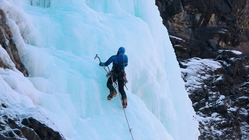 Alpinist climbs on icy wall with high caution