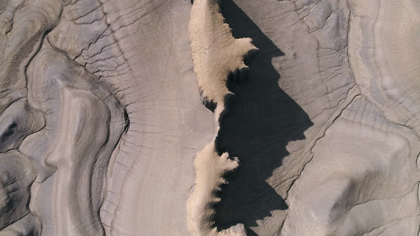 Aerial view looking down at the desert terrain in Caineville Utah slowly moving over top of the skinny cliff walls.