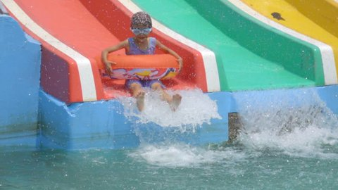 Playing water park concept. Asian cute child slide slow motion on slider in water park on summer holiday. Cute girl is funny and happy playing in water park. Water splash on pool is beauty.
