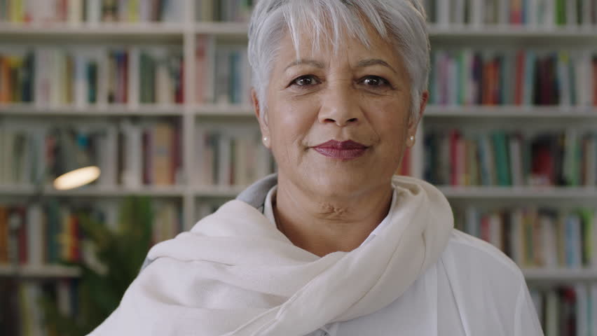 Portrait of friendly indian middle aged teacher standing in library smiling