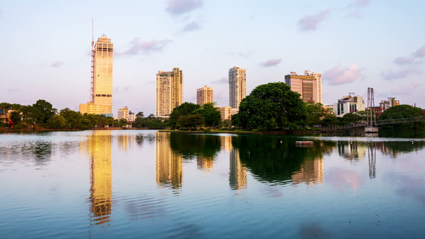 Sri Lanka. View of Beira Lake in Colombo, Sri Lanka with buddhist temple and modern buildings at sunrise. Morning time-lapse. Clear sky