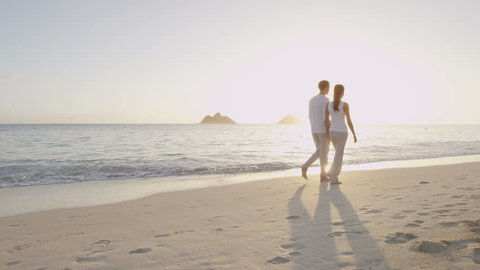 Honeymoon newlywed married young couple on beach walking in love holding hands at romantic sunrise' Multiracial woman and man relaxing on travel vacation holidays on Lanikai Beach, Oahu, Hawaii, USA