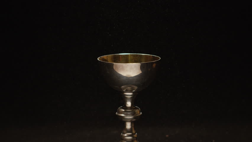 Slow motion wine pouring into golden christian chalice