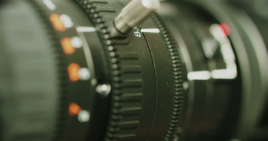 Close-up of a modern TV camera lens -- turning of a zoom and focus rings simultaneously in very shallow depth of field | Shutterstock HD Video #1009587644